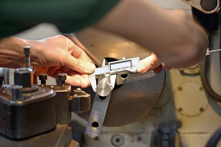 Hände eines schlechten Maschinenbauingenieur während der Messung ein metallisches Stück mit einer genauen Sattel an Werkbank