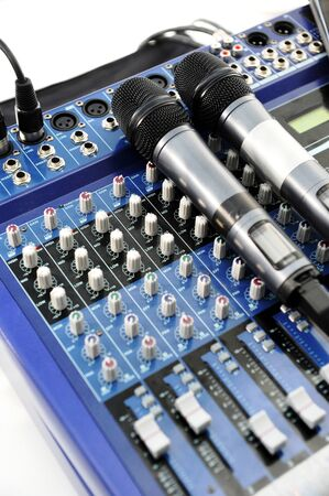 verbal: Mixer and microphones on a studio deck with audio control knobs and sliders for broadcasting and recording in an entertainment concept, close up high angle view