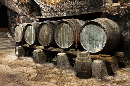 casks: Row of old wooden oak barrels in a wine cellar on a winery for the production and maturing of local wines