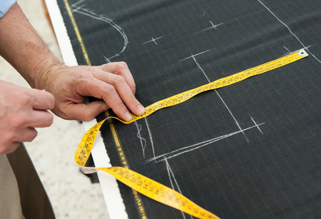 perfect fit: Tailor or clothing designer marking out a pattern for a handmade garment on a length of textile measuring to ensure a perfect fit for his client