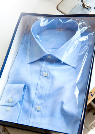 gent's: New light blue elegant shirt for men with white buttons and long sleeves designed in classical fashion style, folded in a transparent plastic pack for sale, close-up Stock Photo