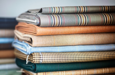 cloth manufacturing: Folded fabrics for interior decor or garment making by a tailor or seamstress in a neat stack in a shop or studio
