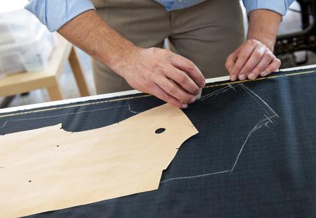 marking up: Adaptar o dise�ador de ropa en el trabajo en su estudio marcando un patr�n de una prenda en un trozo de tela con tiza, de cerca de las manos