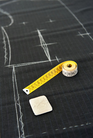 cloth manufacturing: Tape measure in a clothing design studio or tailor lying on a length of fabric with a pattern marked out in chalk ready for cutting Stock Photo