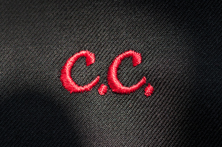cloth manufacturing: Embroidery of initials or clothing logo with C.C. in red stitching on a dark fabric in a needlework, tailor, seamstress or clothing manufacture concept