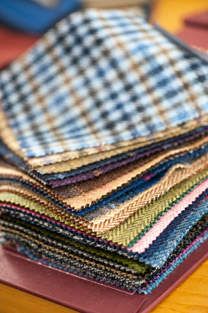 fabric textures: Fabric samples or swatches of various textiles for garment making in a tailors shop or seamstress showing an assortment of colors and textures