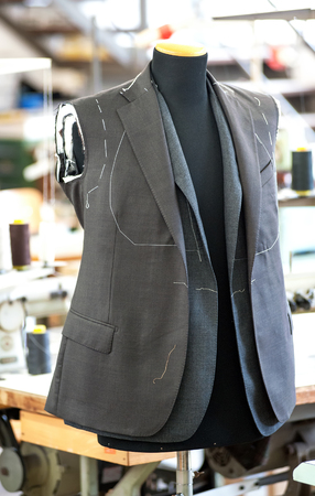 Partially completed hand tailored jackets hanging on a mannequin in a clothing design studio, seamstress or tailors workshop