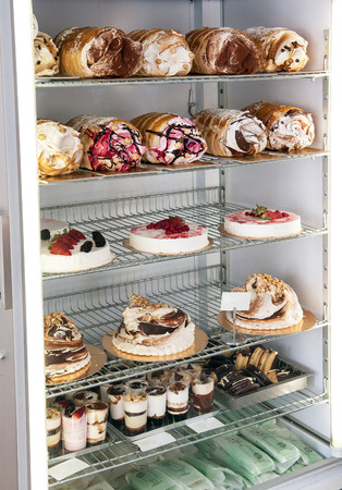 flavours: Display of traditional Italian semifreddo cakes and desserts in a refrigerator made from semi frozen ice cream and cream whipped into a mousse parfait and flavoured with assorted fruits and flavours