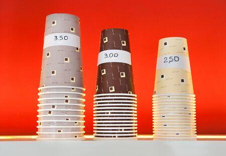 Trois piles de tailles assorties de papier ou de carton milk-shake gobelets jetables marqués avec leurs prix se tenant prêt sur une étagère dans un salon magasin ou la crème glacée sur un fond rouge