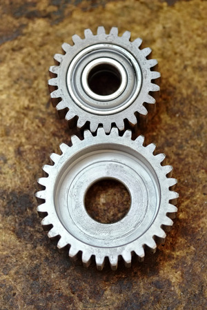 meshed: Two new toothed gear wheels meshed sall and one larger one lying on a wooden surface in an engineering workshop overhead view Stock Photo