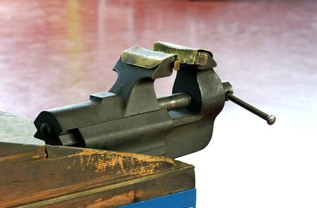 Steel vice mounted on a wooden workbench with metal jaws for gripping and holding components during the engineering or industrial manufacturing process Banco de Imagens