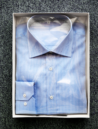 gent's: High Angle View of Tailor Made Blue Button Down Dress Shirt Wrapped in Cellophane and Folded in Open Box on Carpeted Surface Stock Photo
