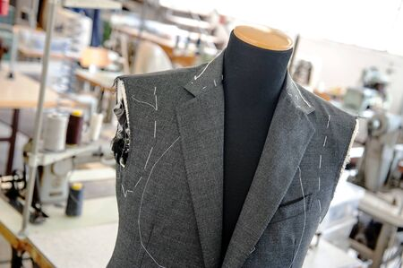 made by hand: Close Up of Custom Made Hand Sewn Jacket in Progress on Mannequin Inside Clothing Manufacturing Factory or Shop Stock Photo