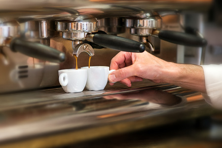 brew house: Close up view of the hand of a man working in a coffee house preparing espresso coffee waiting for the coffee machine to finish pouring the fresh beverage into two small cups