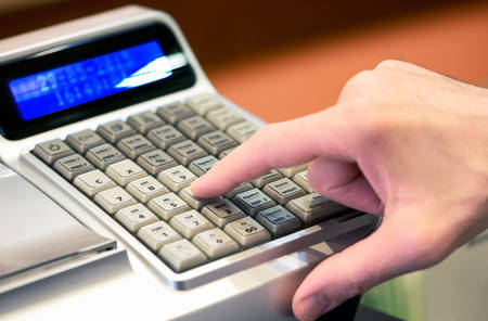key punching: Close up of the hand of a person entering a sale on a cash register punching in the amount on the key pad with a view of the digital readout