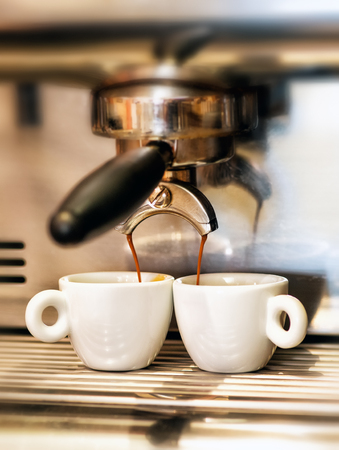 expressed: Coffee machine dispensing a double Italian espresso into two small cups in a coffee house or restaurant
