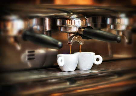 Italian espresso machine on a counter in a restaurant dispensing freshly brewed coffee into two small cups to be served to customers