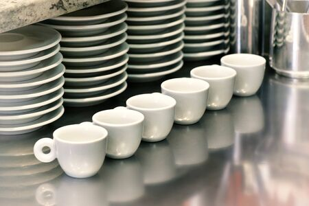 handouts: Small coffee cups lined up on a metal cafeteria or coffee house counter with stacked saucers behind ready to serve customers Stock Photo