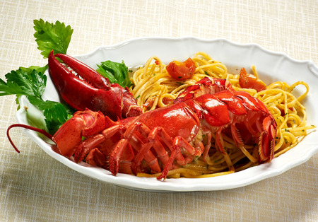 Close up Gourmet Tasty Healthy Red Lobster with Linguine Pasta Recipe on White Plate Served on the Table.