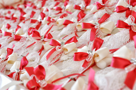 party favors: Close up Plenty of Attractive Party Favors for Guests with Red and White Ribbon Designs, Placed on Top of the Table