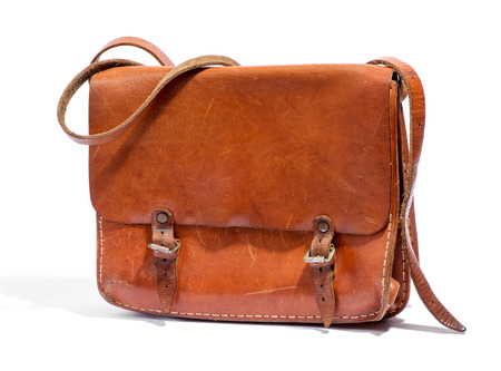 buckles: Old brown leather bag with a shoulder strap and buckles, fashion accessory, close up over a white background Stock Photo