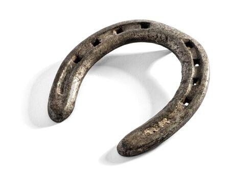 talismán: Herradura metal forjado Vieja para proteger caballos pezuñas, un símbolo de buena suerte y un talismán, más de blanco con la sombra en un ángulo oblicuo Foto de archivo