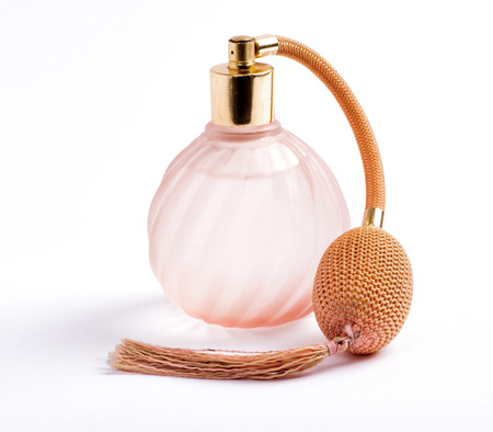 Classic perfume bottle with an atomiser pump for spraying the scent with attached long tassel in ridged swirling pink glass over white Stock Photo