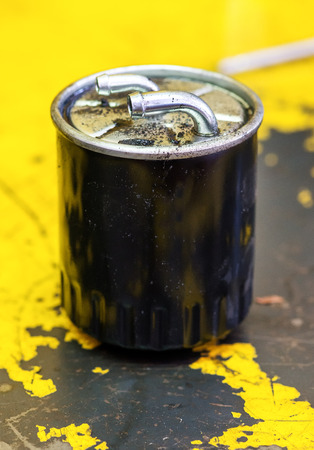 replaced: Used diesel oil filter standing on a workshop floor after being removed and replaced during a service in a garage Stock Photo