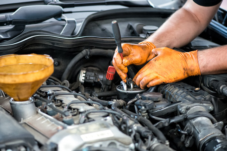 automotive mechanic: Mecánico trabajando en un filtro de diesel, de cerca