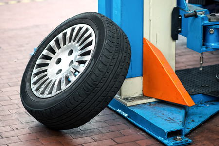 Car wheel leaning up against the support of a hoist or elevator in a garage or repair workshop