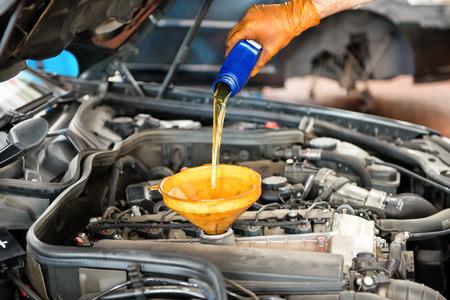 Mechanic Nachfüllen das Öl in einem Auto einen halben Liter Öl durch einen Trichter in den Motor Gießen, in der Nähe seiner Hand und das Öl