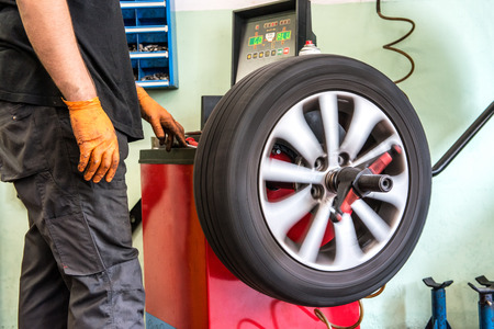 Mechanic balancing a car wheel on an automated machine checking the readout on the digital display before adding the weights