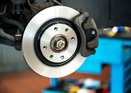 automotive repair: Brand new brake disc on car in a garage