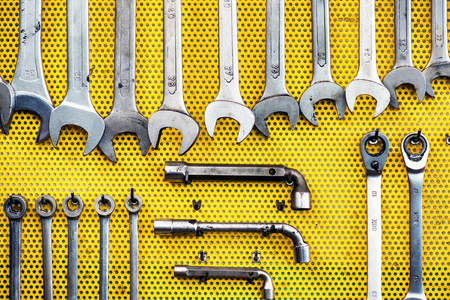 neat: Neat arrangement of tools on yellow pegboard in a workshop with spanners, wrenches and sockets
