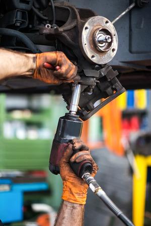 mantenimiento: Trabajador que hace el mantenimiento en el coche con el taladro