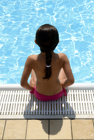 ponytail: Young woman with a ponytail sitting on the tiles at the edge of sparkling blue swimming pool in her bathing costume, high angle view from behind