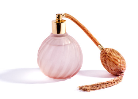 tassel: Swirling decorative glass pink perfume bottle and atomizer with bulb and tassel for vintage style packaging of fragrance and scent, on white with a shadow Stock Photo