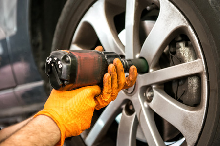 mecanico: Mecánico que trabaja en un endurecimiento de la rueda del coche o aflojar los tornillos en el cubo y la llanta con una herramienta de energía eléctrica, vista de cerca de las manos Foto de archivo