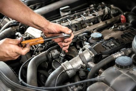 mechanic: Mecánico con una llave y el zócalo en el motor de un automóvil durante un servicio o la reparación en un taller automotriz, de cerca de las manos Foto de archivo