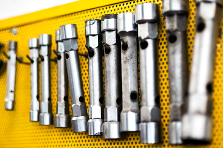 diameters: Set of interchangeable sockets of different diameters hanging on yellow pegboard in a workshop, oblique angle view