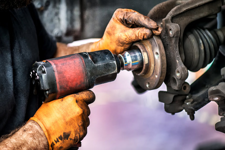 Powerful mechanic hand drilling on a car wheel Stock Photo