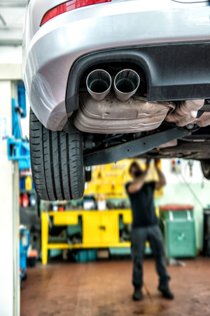 Monteur reparatie van een auto op een takel in een werkplaats met nadruk op de achterste uitlaatpijp met de monteur aan het voorzijde van het voertuig op de achtergrond Stockfoto