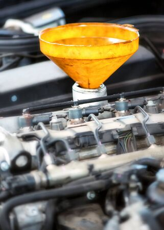 sump: Yellow plastic funnel for motor oil inserted in the feeder pipe in the engine during a routine service or repair in an automotive workshop