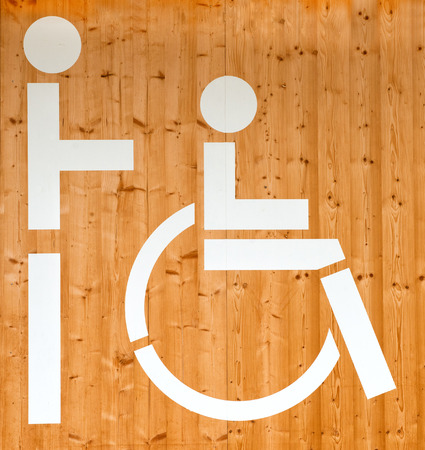 wheelchair access: Disabled sign showing a person in a wheelchair on a wooden wall depicting handicapped access or a facility reserved for disabled persons Stock Photo