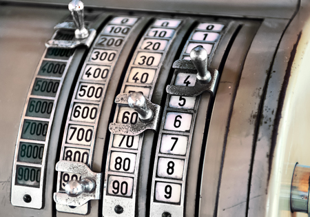 denominations: Vintage cash register with columns of numbers in different denominations with manual metal levers to record the amount or price