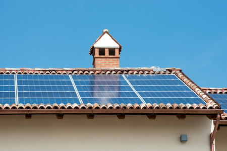 natural resource: Photovoltaic solar panels on the roof of a building for providing green electricity from the conversion of solar energy, a sustainable natural resource Stock Photo