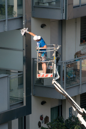 picker: Workman on an elevated mechanical platform or industrial cherry picker standing working on the exterior of a building in his shorts and cap on a hot summer day