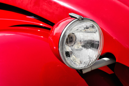 coachwork: Close up detail of the raised round front headlight on a red vintage car with decorative black stripes on the coachwork