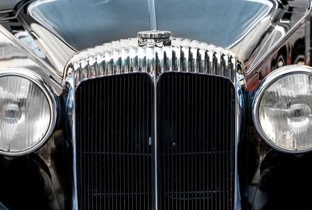 coachwork: Close up of the headlamps and decorative chrome around the front grille of a vintage car with black coachwork Stock Photo