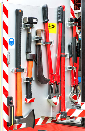voiture de pompiers: Collection of fire fighting tools and equipment neatly mounted on a metal panel on a fire engine or fire fighters vehicle ready for emergency use